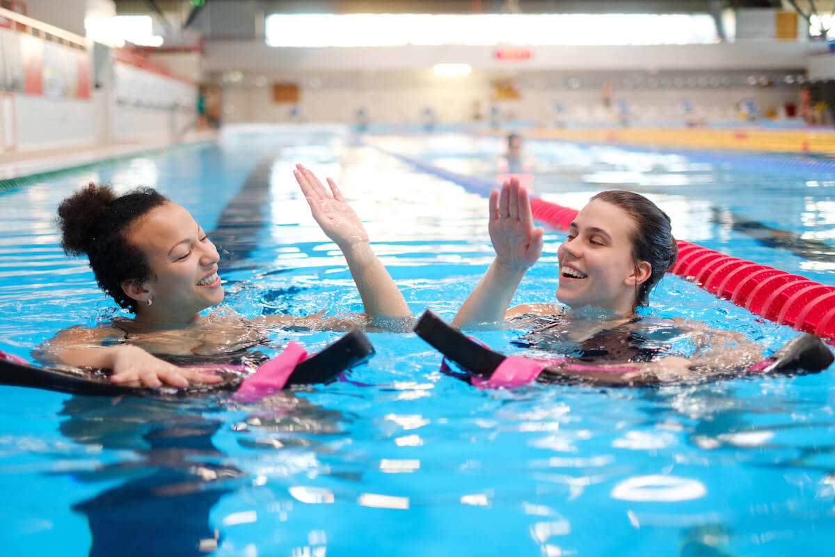 Two women high fiving after doing aquatic therapy