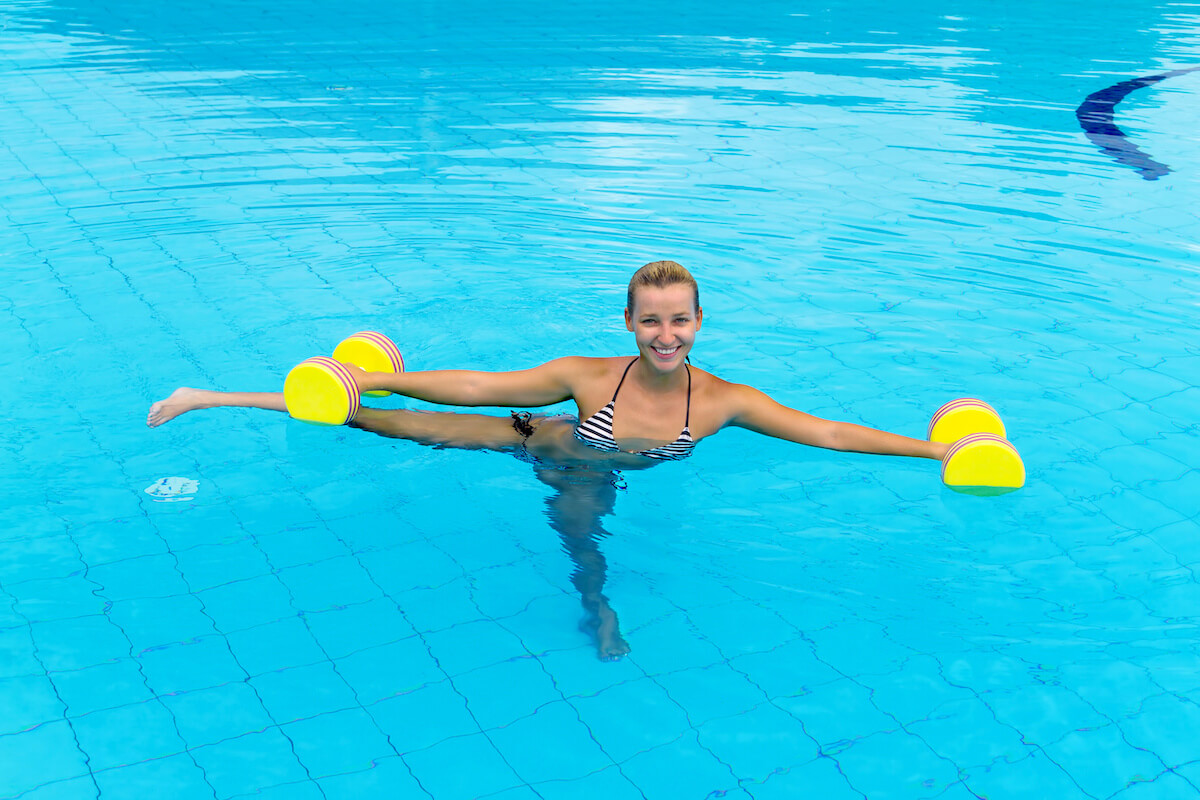 Woman doing an aquatic therapy exercise with weights