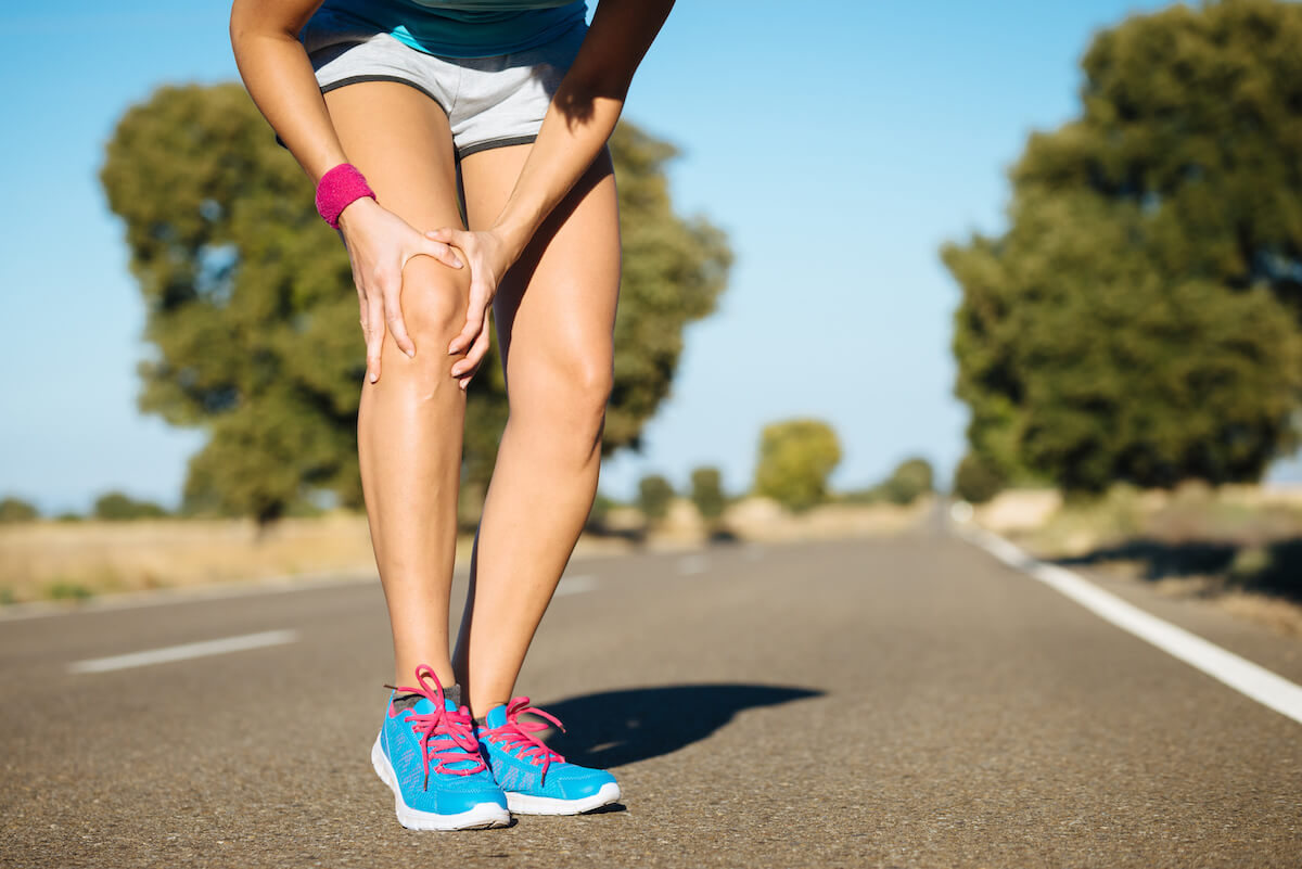 Woman running stops to hold her knee in pain
